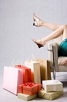 Young woman lying on sofa with feet up and shopping bags and gift box on the floor