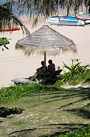 Two person sitting under a sunshade at beach