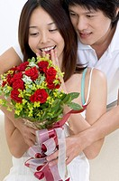 Young man giving a bunch of flowers to his girlfriend