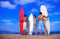 Three people holding the surfboards and standing on the beach