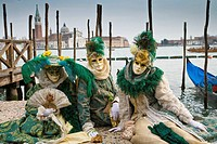 A group of masked persons at the carnival in Venice sitting at the pier in front of San Giorgio Maggiore in Venice, Italy, Europe