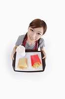 Young waitress holding fast food on the tray