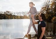 Man helping wife balance on fence near pond