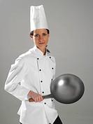 Junge Koechin schwingt die Pfanne, young cook swinging the pan