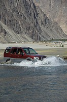 Jeep passing through a lake with mountain range in the background, Hunder, Nubra Valley, Ladakh, Jammu and Kashmir, India