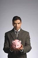 Portrait of a businessman holding a piggy bank
