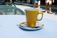 Coffee cup on a table at a sidewalk cafe, Athens, Greece