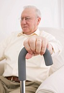 Senior man with hand on walking cane, close_up