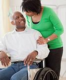 African woman pushing husband in wheelchair