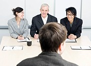 Three people interviewing a candidate in an office