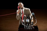 African man talking on telephone at podium with microphones