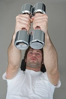Young man lying on weight bench holding dumbbells