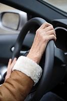 Woman holding car steering wheel