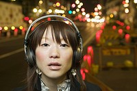 Young woman standing on street and wearing headphones, Tokyo, Japan