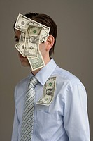 Businessman with money stuck on his head