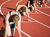 Group of male athletes in starting blocks on a running track