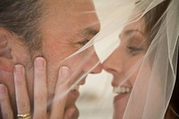 Close_up of a bride and a groom embracing