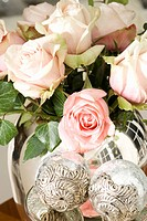 A bouquet of pale pink roses in a silver vase