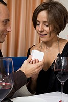 A man giving a woman a ring in a restaurant