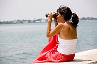 Side view of a woman using binoculars by the sea