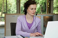 A young woman wearing a telephone headset whilst working on a laptop computer