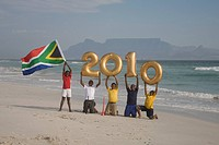 Young boys on beach, holding South African flag and golden balloons with numbers 2010, Table Mountain in background, Blouberg Beach, Cape Town, Wester...