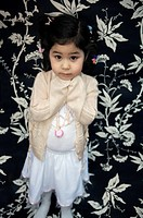 A High Angle View portrait of a young girl with a floral pattern backdrop