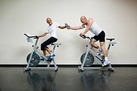 A senior woman and a mature man riding stationary bikes and passing a water bottle