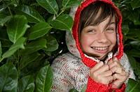 A young girl hiding in a bush