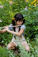 A young girl playing a flute in nature