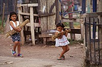 Two children carry wood