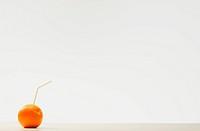 An orange with a straw