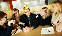 Man with flimsy crown on head and women paying attention to him