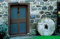 Architectural exterior of stone wall, door and millstone