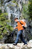 Man hiking in the Gorge, Crossing a stream, Partnachklamm, Garmisch_Partenkirchen, Bavaria, Germany