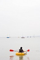Young man in a rubber dingy, Lake Ammersee, Bavaria, Germany