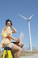 Young woman sitting on ladder with laptop near wind farm.