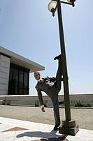 Portrait of young businessman doing standing split against lightpost