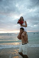 Bridegroom carrying his bride on the shoulder at the beach