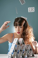 Contemplative young woman making pyramid of playing cards