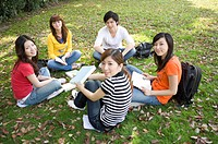 Five young college students sitting on the lawn and studying together, Studying, Education