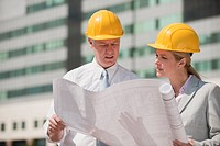 Two architects holding plans outdoors