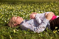 man with baby sleeping in grass