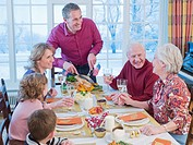 Man carving turkey for multi_generation family at table