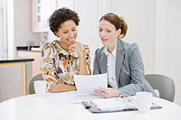 Businesswoman reviewing paperwork with woman