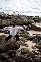 A man stretching on a rocky beach in Koh Lanta, Thailand