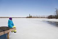 Woman Relaxing on Dock by Frozen Lake