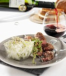 Lamb kebabs with side salad, pouring red wine