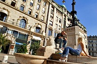 Hungary, Budapest, Varasmarty Square, young people sitting on the steps of the Lions Fountain