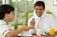Close_up of a mature man using a mobile phone beside his son at a breakfast table